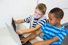 教育孩子使用膝上型计算机和数字式片剂在教室 免版税库存照片