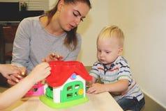教育家处理孩子在幼儿园 孩子的创造性和发展 免版税库存图片