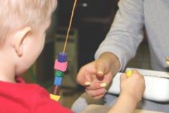 教育家处理孩子在幼儿园 孩子的创造性和发展 免版税库存照片