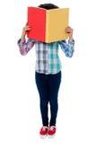 教育掩藏她的与书的女孩面孔 免版税库存图片