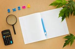 教育有笔记本、笔、计算器、放大器和数字的书桌 免版税库存照片