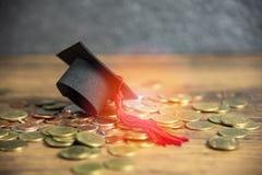 教育概念毕业盖帽的奖学金在金钱硬币木桌上 免版税库存图片