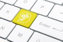 教育概念:有齿轮的头在键盘backgrou 免版税库存图片