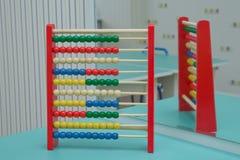 教育概念-有许多五颜六色的小珠的算盘 孩子的手工计算器 明亮的木玩具算盘 玩具 库存照片