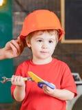教育比赛概念 使用与玩具工具的孩子 拿着橙色防护盔甲的男性手 免版税库存照片