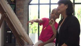 教育非裔美国人的孩子艺术和教如何的年轻老师绘在客厅里面的画架 股票录像