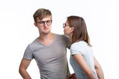 教育,人概念-玻璃的两三年轻人看,如他们是站立在白色的书呆子 免版税库存照片