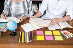 教育,教学,学会概念 坐在有帮助朋友做的图书馆里的两个高中生或同学小组 免版税库存照片