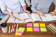 教育,教学,学会概念 坐在有帮助朋友做的图书馆里的两个高中生或同学小组 库存照片
