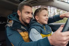 教逗人喜爱的矮小的儿子的微笑的父亲驾驶汽车 免版税库存照片