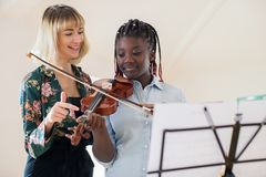 教高中学生的家庭教师弹在音乐Lesso的小提琴 免版税图库摄影