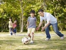 教练儿子的父亲踢足球 免版税库存照片