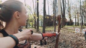 教练员命中女性手拿着弓箭的,因此她射击 股票视频