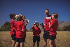 教练员和孩子饮用水在新兵训练所 图库摄影