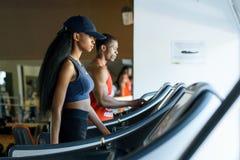 黑教练员和性感的非裔美国人的妇女踏车的在健身房 球概念健身pilates放松 免版税库存图片