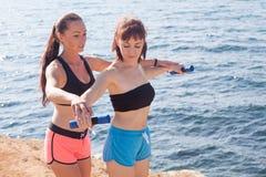 教练员帮助女孩做锻炼 免版税库存照片