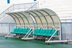 教练和储备长凳在橄榄球场内 库存照片