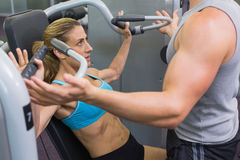 教练女性爱好健美者的个人教练员使用重量机器 库存图片