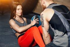 教练帮助健身房的一个年轻美丽的女运动员 免版税库存图片