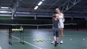 年轻教练教一个成人男孩保留正确的球拍,学生,并且他的大师在网球俱乐部,人们 股票录像