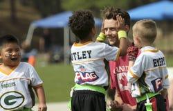教练旗标橄榄球队的一个年轻人 免版税库存图片