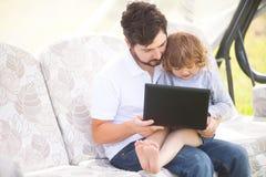 教他的女儿的父亲使用便携式计算机 库存图片