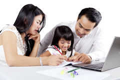 教他们的女儿的年轻父母画 库存照片