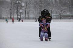 教他的孩子的父亲滑冰 库存图片