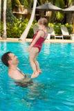 教他的小孩女儿的活跃父亲游泳在热带手段的水池在泰国,普吉岛 免版税库存图片