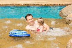 教他的小孩女儿的活跃父亲游泳在热带手段的水池 图库摄影