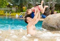 教他的小孩女儿的活跃父亲游泳在热带手段的水池 免版税库存图片