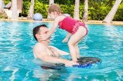 教他的小孩女儿的活跃父亲游泳在热带手段的水池 库存照片