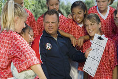 教练谈论战略与女孩足球队员 库存图片