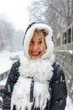 敞篷和白色围巾的滑稽的女孩显示她的舌头 免版税库存图片
