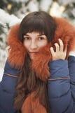 敞篷的棕色毛发的女孩有毛皮的微笑在积雪的树背景的  免版税库存照片