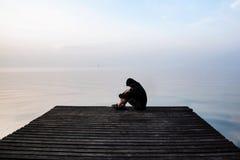 敞篷的沮丧的消沉人坐木桥, 免版税库存照片