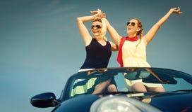 敞篷车汽车的两名妇女享受汽车旅行的 图库摄影