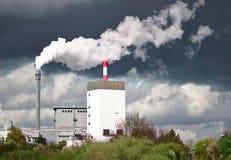 散发在黑暗的雨云前面的水电站白色蒸汽 图库摄影