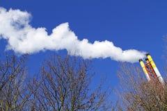 散发天空烟的蓝色烟囱 免版税库存照片