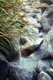 散发烟的小河含硫水在Owakudani,在箱根地区,日本 免版税库存照片