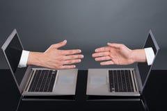 散发从膝上型计算机的商人的手代表成交 免版税库存图片