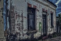 散开在与多云天空的黄昏的肮脏的老房子 免版税图库摄影