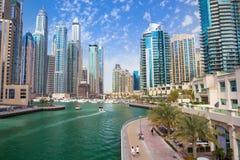 散步和运河在有豪华摩天大楼的迪拜小游艇船坞,阿联酋 免版税库存照片