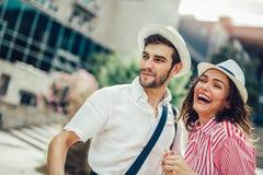 散步在一条城市街道边路的游人在一个晴天 免版税库存图片