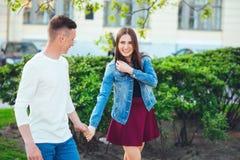散步在一条城市街道边路的游人夫妇在一个晴天 库存图片