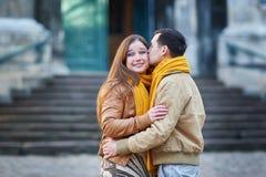 散步在一条城市街道边路的游人夫妇在一个晴天 免版税库存图片