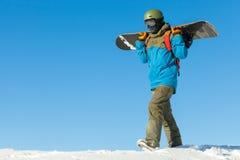 散步在与美丽的天空的一座山顶部的年轻挡雪板在背景 库存图片