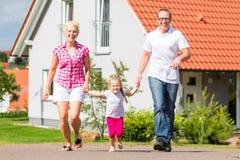 散步在家前面的家庭 免版税库存照片