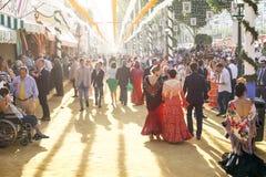 散步在日落的人们,获得乐趣和穿戴在传统服装在塞维利亚` s 4月市场 库存照片