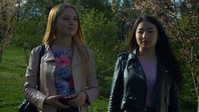 散步在春天公园的微笑的不同的女孩 股票录像